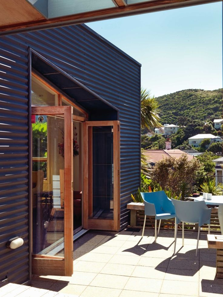 Painted corrugated exterior walls flank the outdoor area at the front of the house