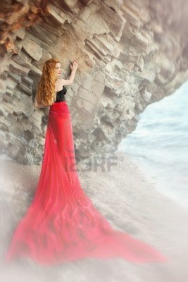The beautiful red-haired girl poses on a sandy beach Stock Photo