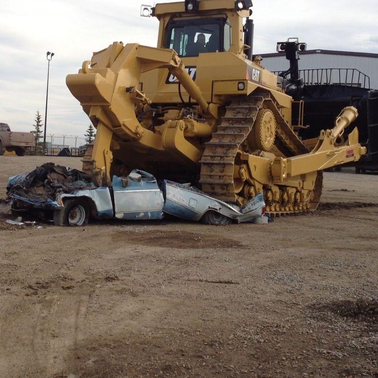 Caterpillar D11T bulldozer crushing a truck.