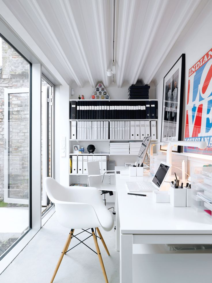 The office, which is a single-level separate unit, boasts Ikea desks and a signed work by Gilbert and George (friends of the couple). Photo by Mark Seelen.