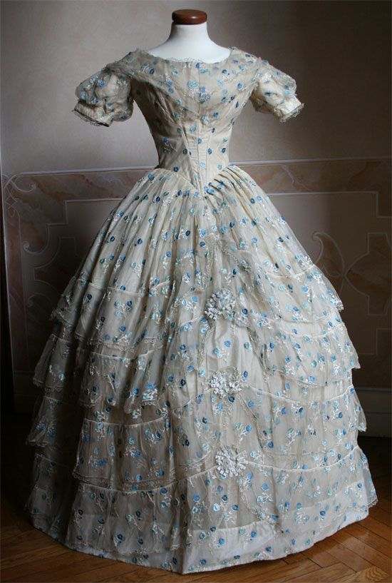 Full ballgown in ivory taffeta coated ivory silk veil embroidered in blue and blue flowers. The top is closed behind a series of hooks. Circa 1852