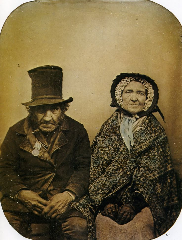British veteran and his wife. He is wearing a top hat, coat and medal, she a bonnet with ruffles, paisley shawl, and gloves. He appears to be wearing a British Crimean War medal with bars. (or maybe Waterloo) // Ambrotype,1860s