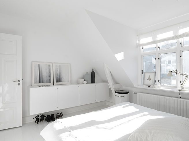 On the upper floors, bright white walls and plenty of natural light makethe bedrooms and living rooms feel large and spacious. In the master bedroom, built-in cabinetry hides clutter. The art photography against the wall isby Anders Hviid,the bed isHästens,the laundry basket isVipp,and the lamp isFontana Arte.  Courtesy of Vipp.