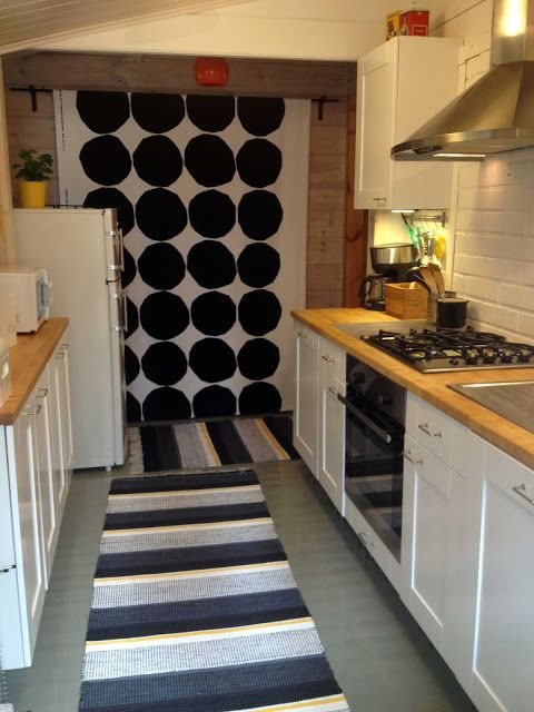 """Liljan Lumo: Cottage renovation. Old sauna was renovated as a kitchen. Marimekko """"Big stones"""" as a curtain and rag rug made by Liljan lumo at the floor."""