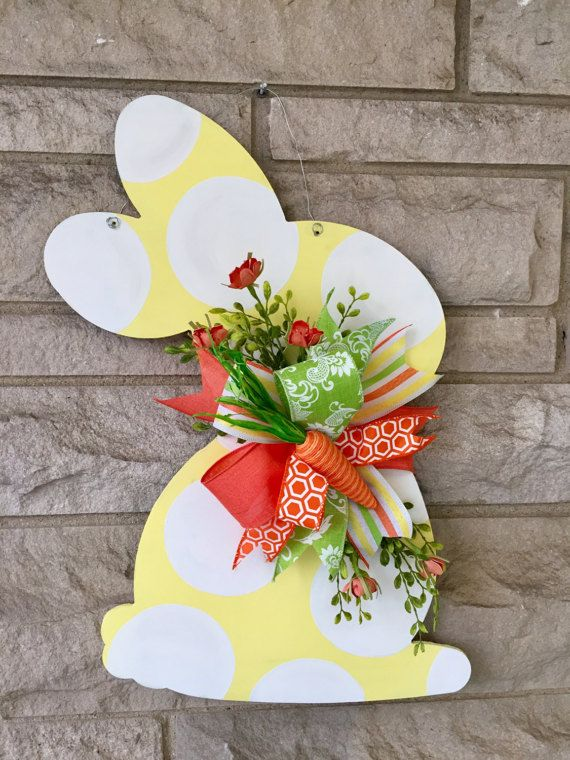 This easter door hanger is made of wood Item measures 22 inches. Comes glittered (doesnt flake) can be left off. This bright and cheerful bunny will make your door the talk of the neighborhood! ** depending on stock ribbon and greenery may vary, but will still be super cute