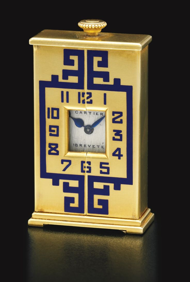 A yellow gold and enamel timepiece, Cartier, circa 1928 manual winding movement, silvered dial, baton indexes, blued steel hands, small 18k yellow gold rectangular case, sprung hinged doors with oriental blue enamel decoration and Arabic numerals opening to reveal three section blue enamel Roman numerals chapter ring, stepped base, pivoting stand, dial signed, case numbered and with French gold marks