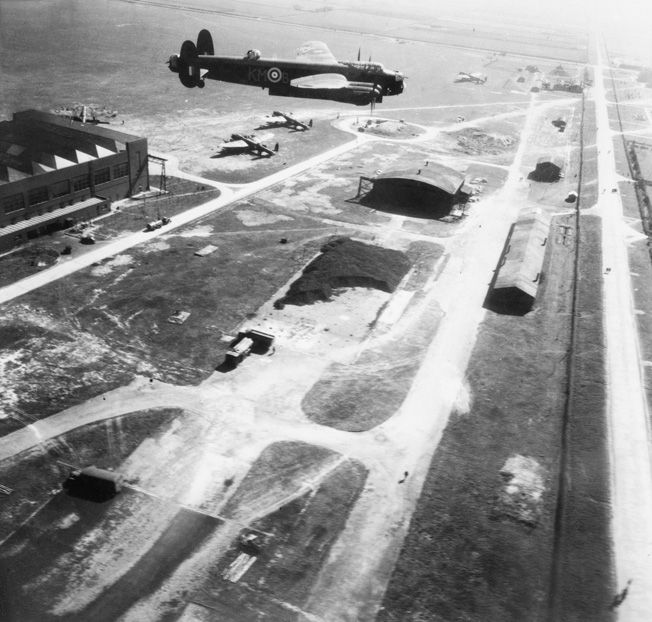 Squadron Leader J.D. Nettleton's Lancaster bomber flies low over RAF Waddington, Lincolnshire, with its bomb bay doors open. This photo was snapped during practice runs for the Augsburg raid, which occurred three days later. The MAN diesel engine assembly plant at Augsburg was a prime target for RAF bombers since it supplied engines to the German U-boat fleet.