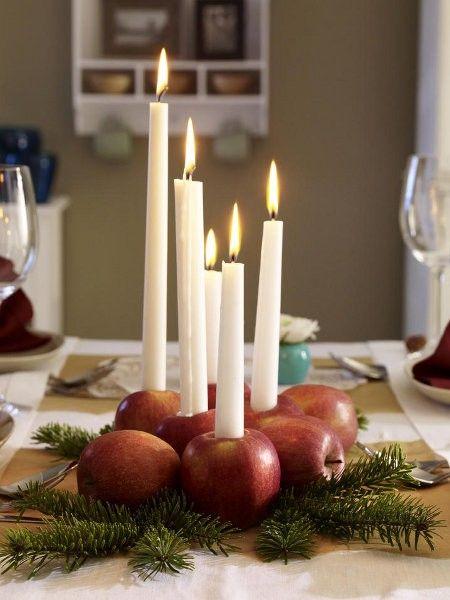 Äpfel als Kerzenständer auf Tannenzweigen