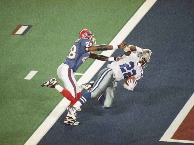Super Bowl XXVIII (Cowboys 30, Bills 13):Cowboys running back Emmitt Smith is hit by Buffalo Bills cornerback Thomas Smith as he scores a touchdown in the third quarter.