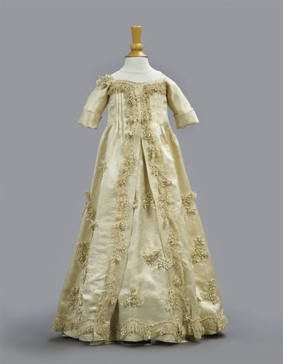 Infant's gown, Europe, second half 18th century. Cream silk with tri-lobed flybraid and silk fringe.