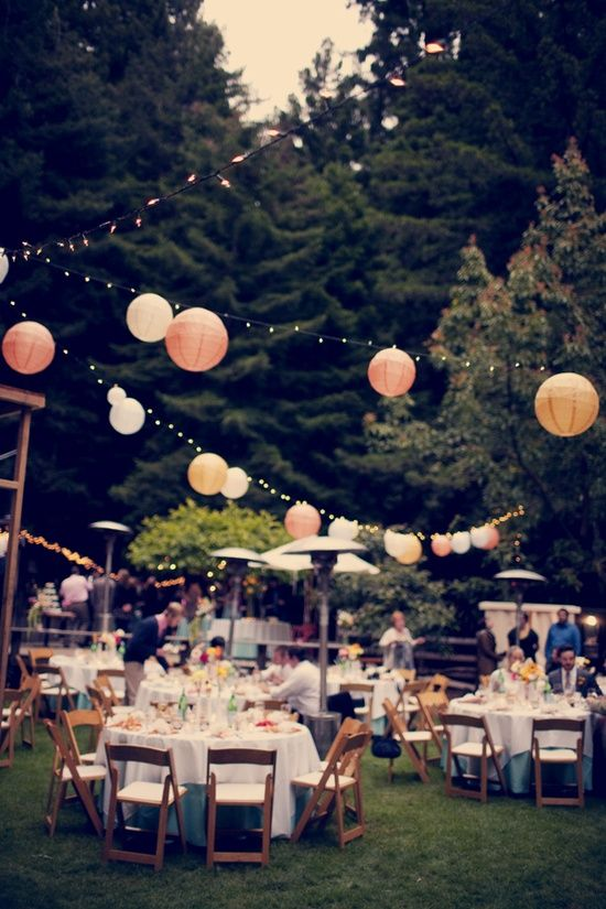 outdoor wedding reception. tissue puff balls hanging on string between trees in the backyard. @Heidi Haugen Haugen Wagner