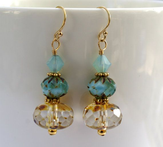 These dangle earrings have beautiful 9x14mm (1/4 in = 6.35mm) crystal clear faceted bottom Czech Picasso beads with hints of blue and brown. There are 9x6mm transparent/opaque sky blue crueller Picasso beads in sky blue. Also, there are 6mm blue opal bicone beads. The ear wires are 14k gold filled and the bottom rondelle beads are gold filled. The spacer beads are gold plate. Earrings measure, from top of ear wires to bottom, approx. a bit over 1-1/2 in. Makes a nice gift ...