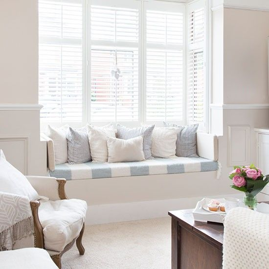 Light filters through white shutters in this classic living room with a blue and white window seat.