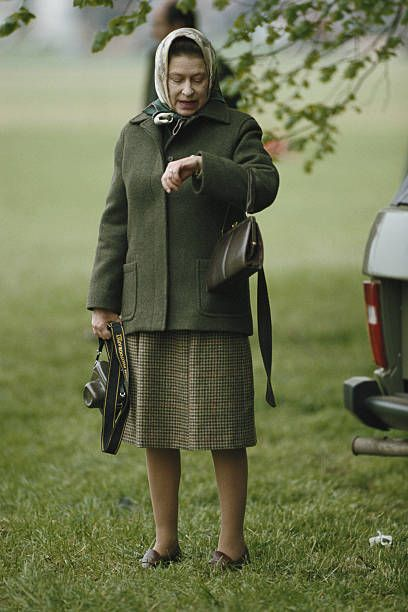 January 01, 1985, Queen Elizabeth II checking her watch at the Royal Windsor Horse Show, held at Home Park in Windsor, Berkshire, England, Great Britain, circa 1985. The Queen is carrying a camera and wearing a headscarf.Less