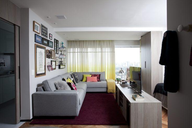 Com a sala de estar e varanda integrados, houve espaço para o generoso sofá da Clami. Repare como a paleta de cinza, verde, rosa e bordô domina o ambiente. Ao fundo, destaca-se a cortina da Riviera Tecidos. Manta sobre o sofá da West Elm, de Nova York, e tapete da Punto e Filo. Apartamento do arquiteta Helena Kallas