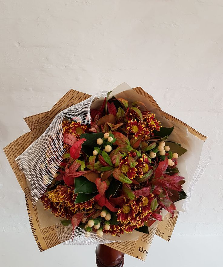 A breathtaking combination of fresh beautiful chrysanthemums, hypericum berries, nandina and magnolia foliage. Order online today at:  https://jaclynroma.com/shop/product/seasonal-flower-bouquet/