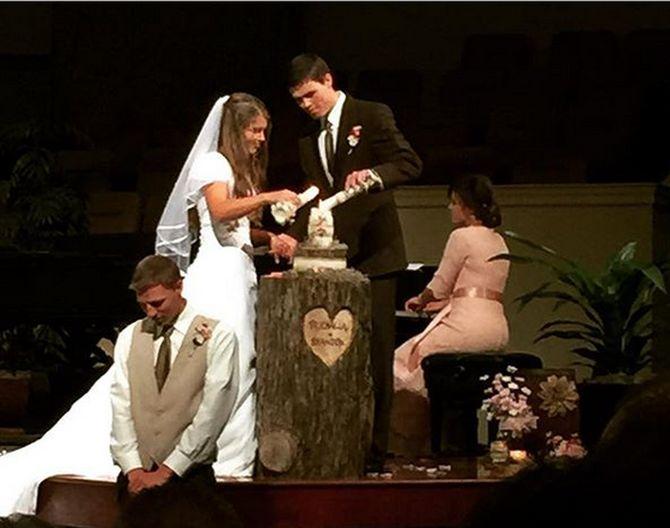 Michaella Bates and Brandon Keilen light unity candle at weddking