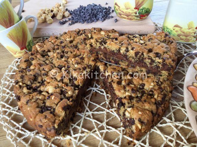 La torta cookies è un grande biscotto di pasta frolla con nocciole tritate e gocce di cioccolato, farcito con crema al cioccolato o nutella.