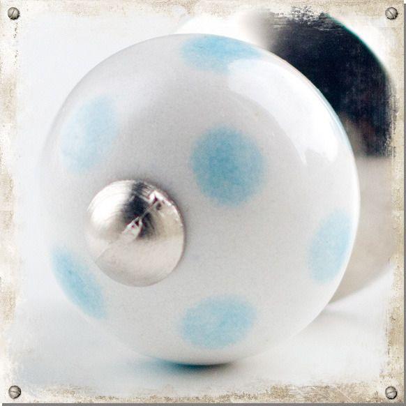 Liten vit knopp i porslin med blåa prickar