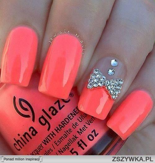 Paznokcie : tego typu paznokcie są koloru jasnego różu  . Ozdobione kokardą i dwoma diamencikami jeden duży a drugi mały a w tle lakier do paznokci o koloru jasnego różu .