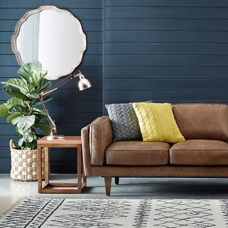 Leather sofa with knitted throw pillows, oversized mirror, dark navy shiplap wall, and graphic print area rug