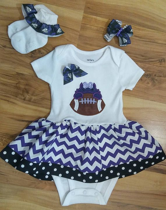 This is a long sleeve (LS) or short sleeve (SS) white, onesie. The onesie has appliqued baby horned frog in purple and a skirt attached in purple chevron with black and white polka dot trim. Name can be added to the football, no extra charge. Message me with the name. Socks and bow can be added as an option. This comes from a smoke-free, pet-free home. I use Carter brand onesies.  Shipping I use the US Postal Service to ship first-class. Please convo or email me if you would like an upgrade…
