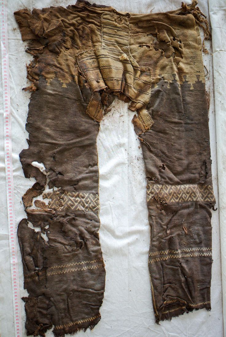 nomadic horsemen: oldest known trousers | 3 uncut woven loom-shaped pieces of brown-colored wool cloth—1 for each leg & an insert for the crotch | side slits + strings for fastening at the waist + woven designs on the legs | Yanghai graveyard, Tarim Basin, China, Central Asia | ~3,000 years old