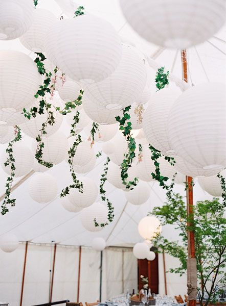 Streamers of short ivy vines and white paper lanterns not only make for a fun and decadent ceiling but also hide tent poles in a cost-efficient way.