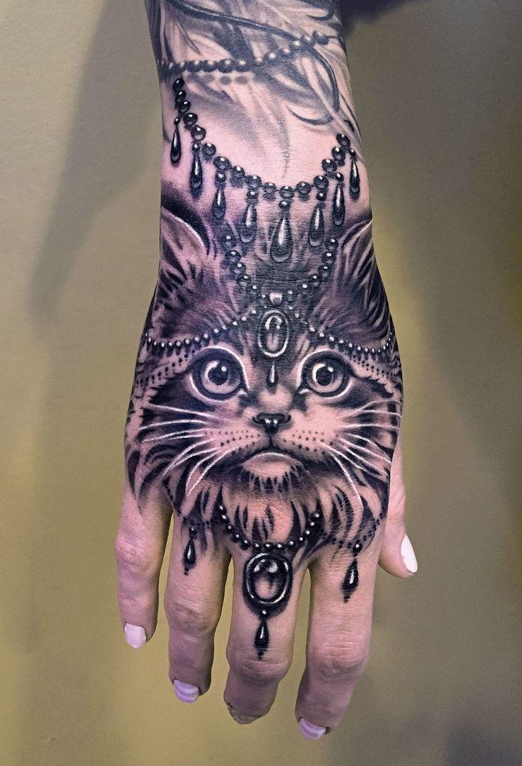 That's an elegant cat and hand tattoo by Ryan Ashley Malarkey...
