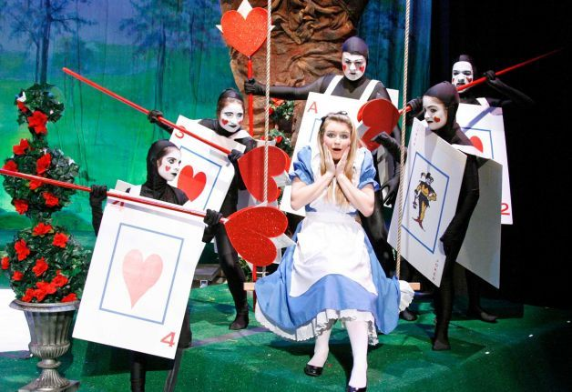 "Alice (played by Elizabeth Koennecke) is frightened by a pack of cards, from left, Margot Weiss, Lauren Peet, Pete Thunem, Berlin Charles and Melissa Calabro during the production of ""Alice in Wonderland,"" which will be staged at New Canaan High School on Nov. 16 and 17. Photo: Contributed / CT"