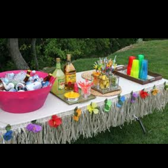 hawaiian luau theme this drinks table is the perfect example of a minimalist effect a little bit of paper grass some coloured flowers and cups