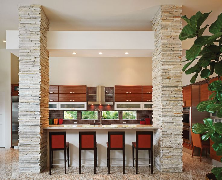 Quartzite-stone columns frame this kitchen, where cherry-wood and stainless-steel cabinetry from Aran World Italian Kitchens pops against white granite countertops from Keys Granite and a tiled cinnamon-colored backsplash from Walker Zanger.