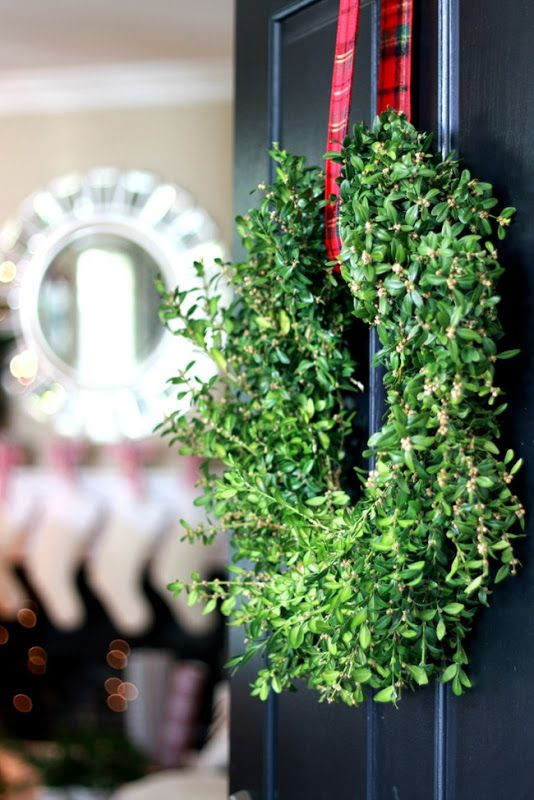 Boxwood wreath, plaid ribbon, black door: