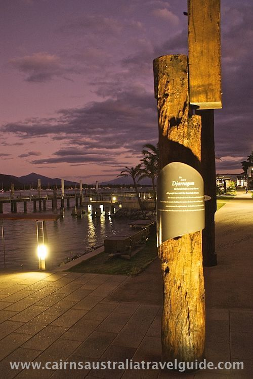Dusk falls over the Cairns Inlet, providing a dramatic backdrop to Indigenous pole sculptures.