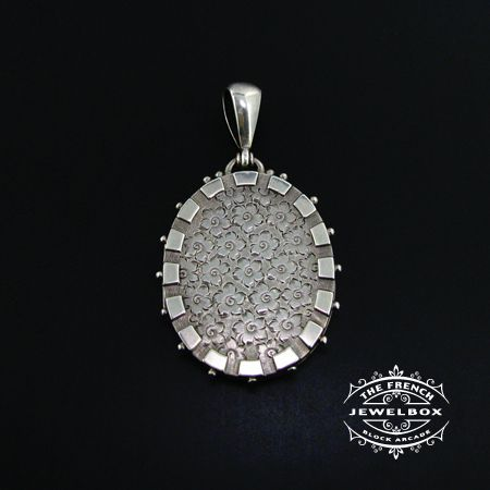 Large sterling silver Victorian locket with shotted edge and engraved flower detail.