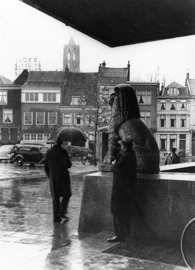 Neude 1938 | Schuilen naast een leeuw. Let op de auto met reclame voor regenjassen.....