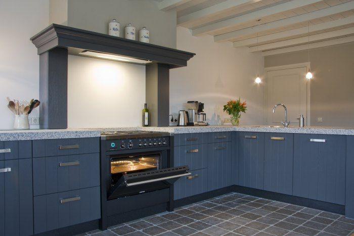 Een keuken in klassiek blauw, voorzien van zeer lux fornuis
