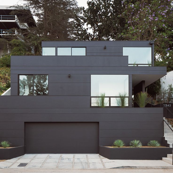 Three black boxes stacked on a steep lot form this residence by Aaron Neubert Architects, and create outdoor living spaces without using additional land.