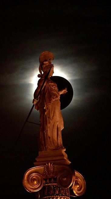 The statue of Goddess Athena is highlighted by the moon, Athens // by (Kostas Tsironis/Associated Press) #