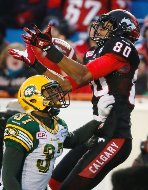 Edmonton Eskimos defender Otha Foster, left, looks on as Calgary Stampeders receiver Eric Rogers makes a touchdown catch during second half of Sunday's Western final.