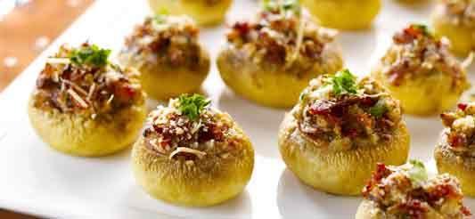 Was de champignons niet, ze nemen teveel vocht op: borstel ze schoon. Breek de steeltjes uit de champignons en schik de hoeden in een met bakpapierbeklede ovenschaal. Wrijf ze in met citroensap en zet opzij. Verwarm de oven voor op T°6 – 180°C.     Snij de steeltjes in kleine stukjes.     Hak de pancetta fijn en bak op matig vuur in een antikleefpan met 1 eetlepel olie. Voeg de fijngesneden uitjes toe (het wit + de helft van het groene deel),...