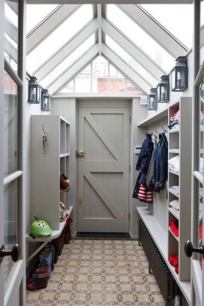 A tidy mudroom designed by Charlotte Crosland Interiors provides lots of light for tracking down essentials with a windowed ceiling and handsome wall sconces above built-in storage units.
