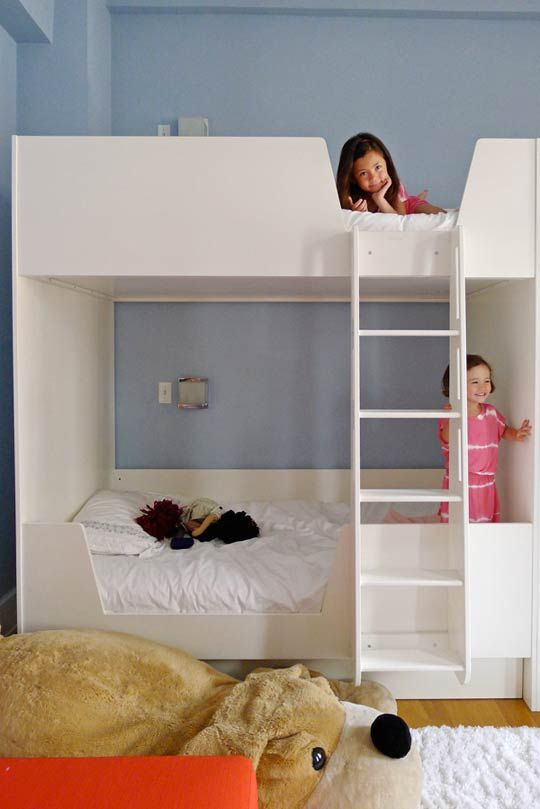 Custom bunk beds for these sisters. The raised ladders allow for more floor space and for a trundle bed to be stored underneath, increasing the room's sleeping capacity to six!