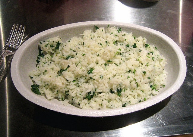 Chipotle's Cilantro Lime Rice Recipe (attributed to CEO Steve Ells)  1 tsp vegetable oil or butter   2 tsp. fresh cilantro  2/3 c white basmati rice  1 c water  1/2 tsp salt  1 Lime  In a 2-quart saucepan, heat oil or butter over low heat, stirring occasionally until melted. Add rice and lime juice, stir for 1 minute. Add water and salt, bring to a full rolling boil. Cover, turn down to simmer over low heat til rice is tender and the water is absorbed, about 25 min. Fluff rice with a fork.