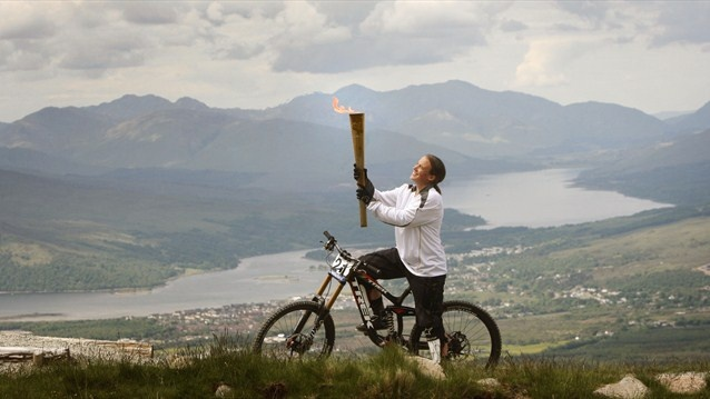 Mountain Biker Tracy Moseley carries the Flame on the Nevis Range during Day 22 of the Torch Relay.