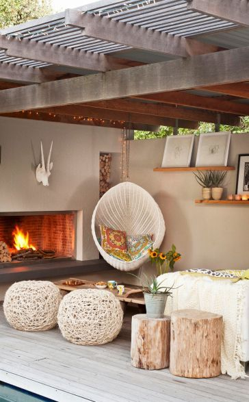 Summer style!! Covered outdoor terrace with a fireplace! Modern Bohemian Chic in neutral colors with lots of textures! Wonderful hanging rattan chair! And the ottoman seating is great too!