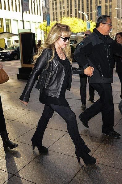 Stevie striding along in her platform boots, wearing a black leather jacket, 2014 ~ so cool   ☆♥❤♥☆
