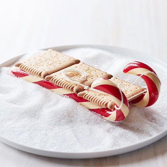 Mit Hilfe von Zuckerstangen könnt ihr aus einfachen viereckigen Keksen Schlitten zaubern.