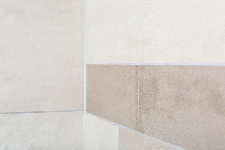 Verschillende formaten en kleuren tegels. Dat klinkt als een drukke combinatie. Deze badkamer bewijst het tegenovergestelde.
