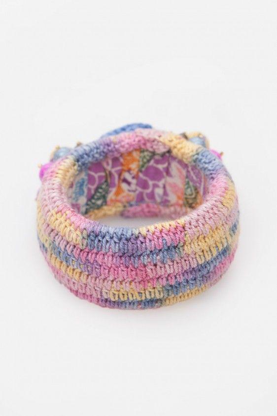 Gelang bungkus rajutan dengan kombinasi warna pink-ungu-biru berhiaskan bunga rajut dan mute dari Ego. Material rajutan. Size: One Size.Diameter 6cm.